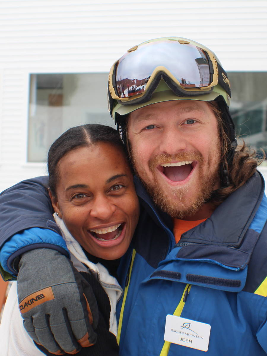 A ski instructor and student sharing a laugh.