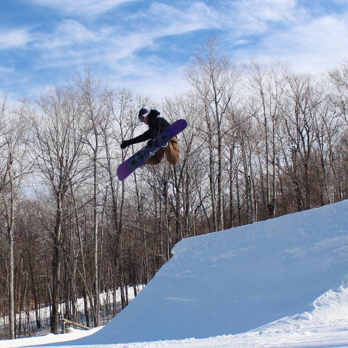 A snowboarder doing a method grab.